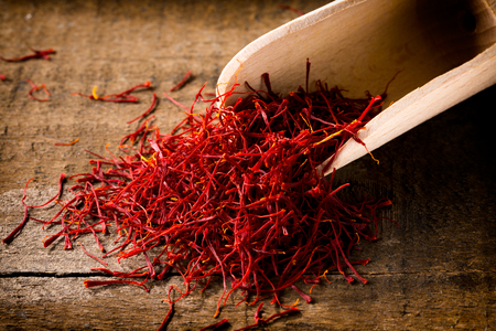 Saffron threads with spice shovel on wooden background, closeup,