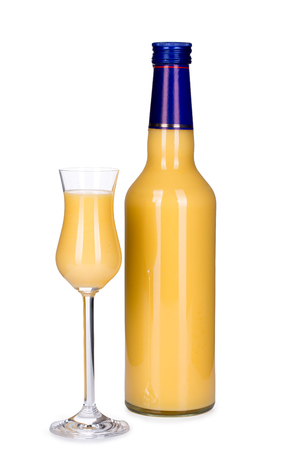 Bottle and glass of egg liqueur isolated on white background, front-view, close-up. Banque d'images