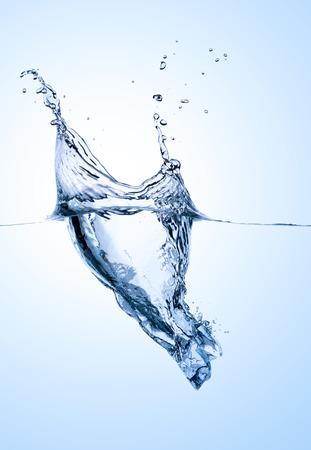 Single ice cube splashing into blue white water