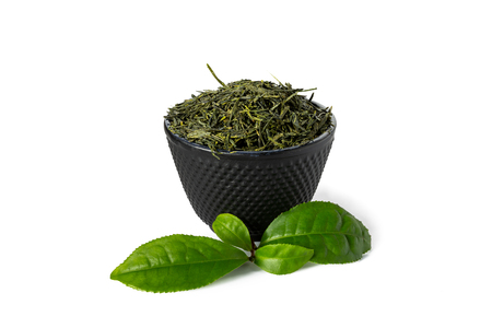 Green sencha tea in black cast iron cup with tealeaves in front isolated on white background. Stock Photo