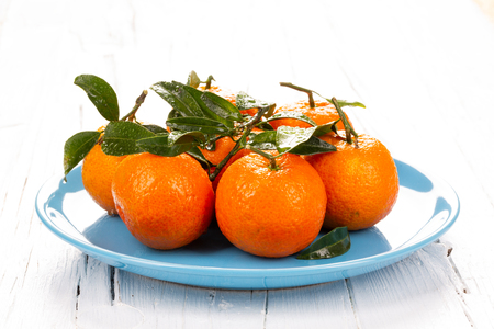 Blue plate with tangerines with green leaves on white wooden board, backlit, contre-jour shot.