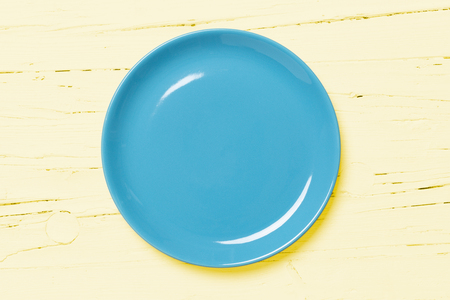 Blue pastel colored plate on bright yellow wooden background, view directly from above