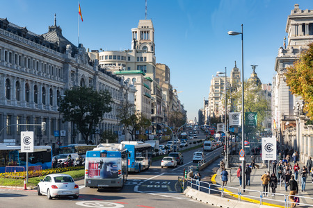 Madrid, Spain - November 29, 2018: Rush-hour on the Calle de Acala traffic circle Paseo del Prado, with cars, buses, pedestrians and motorbikes. Editorial