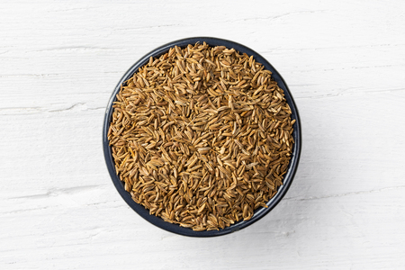Caraway seeds in round bowl on white wooden background, view directly from above.