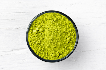 Matcha green tea powder in a bowl on white wooden background, view directly from above.