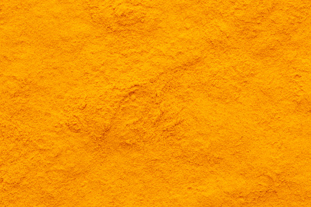 curcuma turmeric spice powder ground full frame image background with rough surface, view directly from above