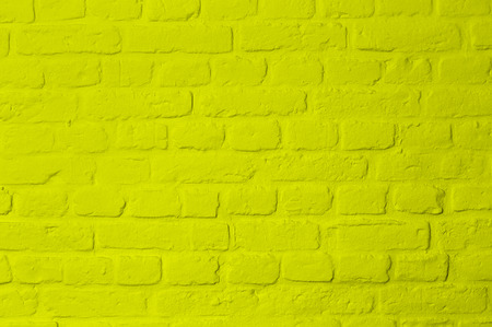 Pastel bright lemon yellow colored brick stone wall, full frame, image background
