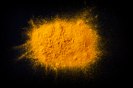 Heap of curcuma turmeric spice on dark black background, top view