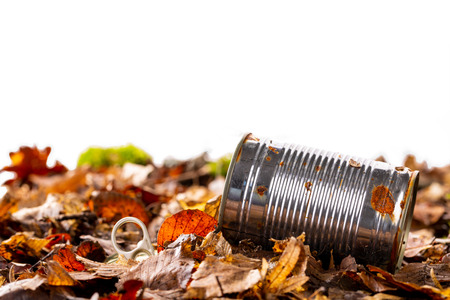 Still life of an rusty empty used tin can with lid and pull waste on forest floor as an environmental pollution closeup