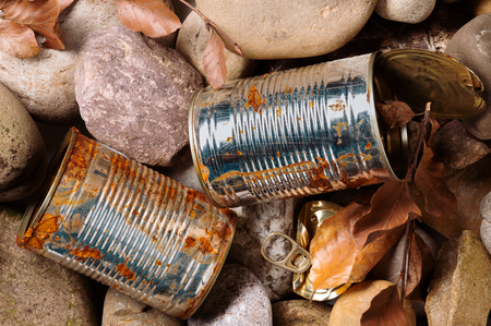Still life of a rusty empty used tin can with lid and pull waste on pebble beach floor as an environmental pollution closeup