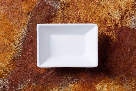Empty white cornered bowl on rusted metal background, top view
