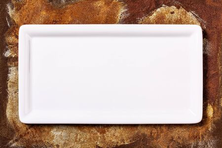 Empty white cornered plate on rusted metal background, top view Stok Fotoğraf