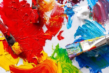 Painter's palette with brushes and colors, top view