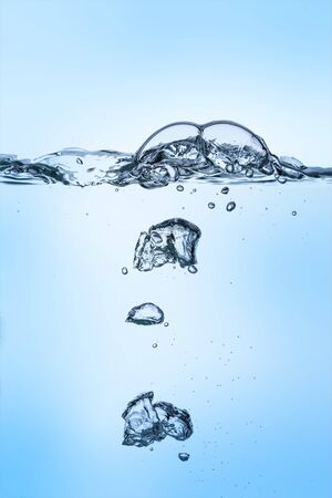 Group of unterwater bubbles rising in clear fresh water on gradient blue background
