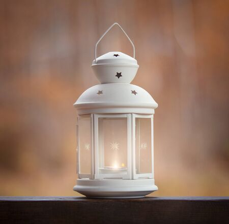 Lantern with a candle on a background of autumn forest