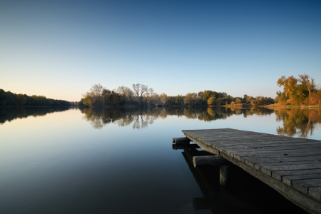 Pier on a lake in autumn photo