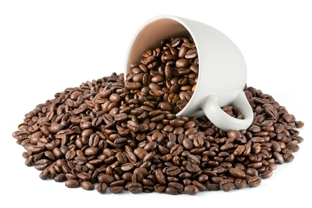 White cup with heap of coffee beans