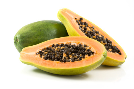 Half cut and whole papaya fruits on white