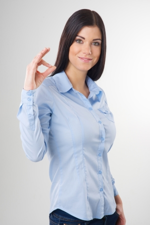 Smiling woman with okay gesture photo