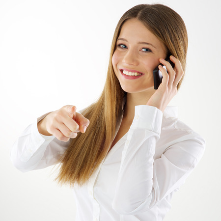 Smiling young woman talking on mobile phone and pointing finger at you photo