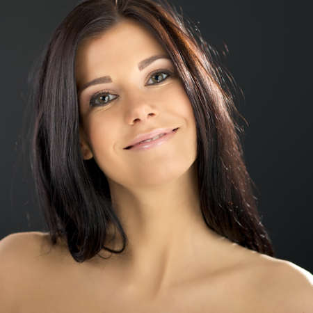 Smiling woman with beauty long brown hair - posing at studio photo