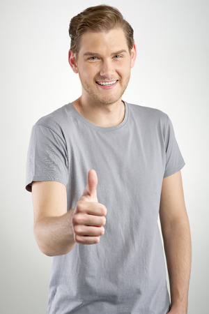Young man gesturing OK sign on light background