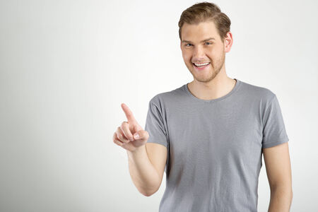 Young man touching an imaginary button on light background with copy space