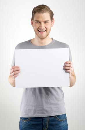 Hombre joven sonriente la celebración de firmar en blanco en las manos