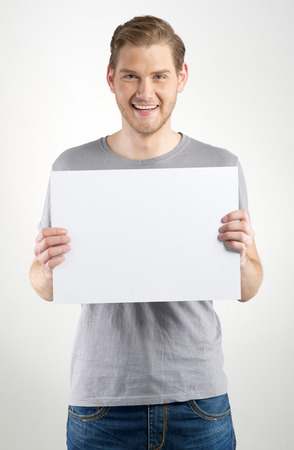 Smiling young man holding blank sign in hands Banco de Imagens - 28712185