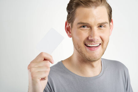 young man holding and showing blank card