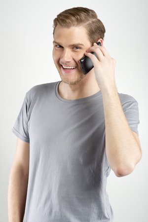 Isolated young attractive man using smart phone  Stock Photo