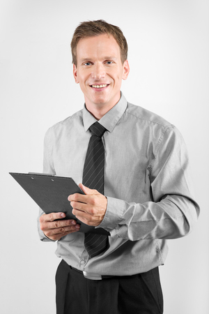 Portrait of young business man with clipboard isolated on white background Stock Photo