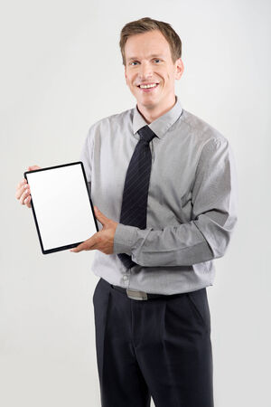 Smiling businessman showing a tablet with empty screen isolated on light background