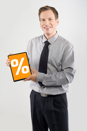 Smiling businessman showing a tablet isolated on light background