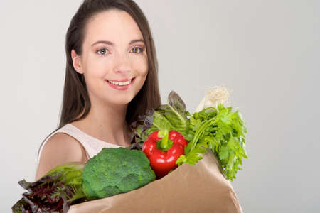 Isolated woman holding a shopping bag full of vegetables Stock Photo