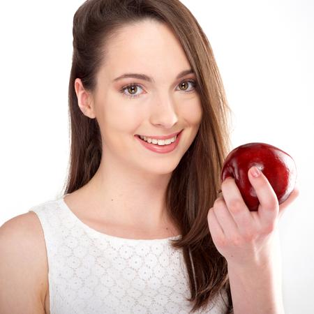 caras: aislado hermosa mujer joven comer una manzana sobre fondo blanco