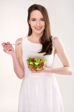 isolated a beautiful girl with salad on light background Stock Photo