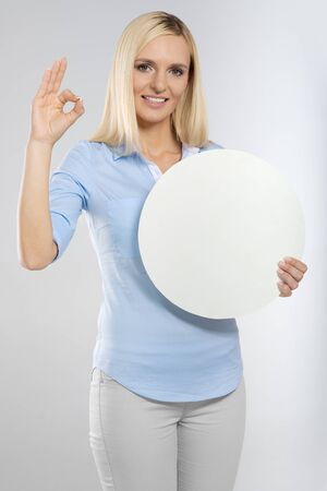 young woman with blank circle board and showing okay gesture