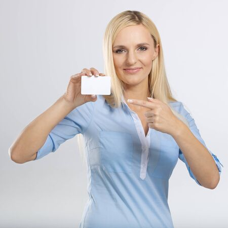 young woman holding and pointing to blank card