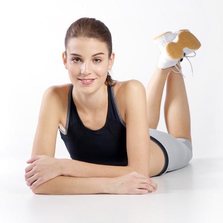 atletismo: Retrato de la muchacha atlética joven hermosa en un fondo blanco