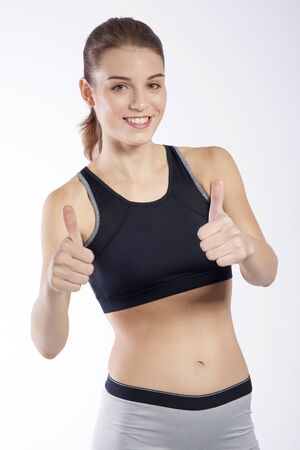Beautiful young woman showing thumbs up Stock Photo