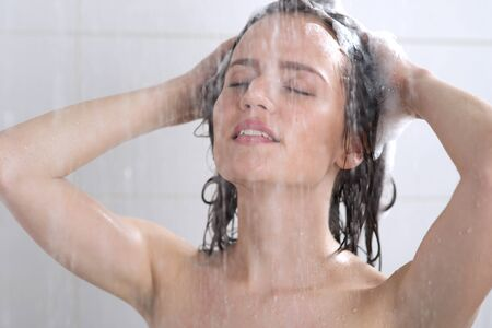 Young woman washing head with shampoo Stock Photo