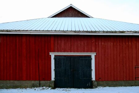 Old red wooden outbuilding with wide doors.