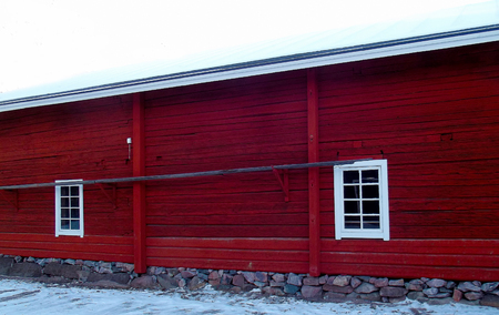 Old red wooden outbuilding with windows. Stock Photo