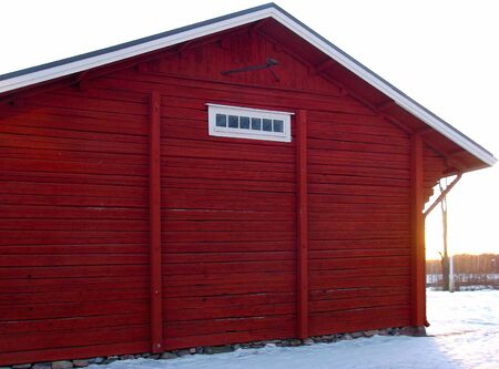 The end of the old red wooden outbuilding. Stock Photo