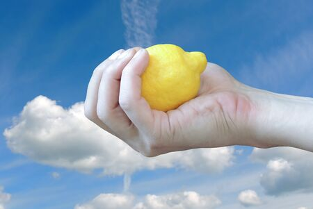 the hand with lemon against the sky with clouds