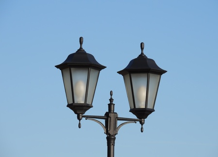 a lone street lamp against the blue sky photo