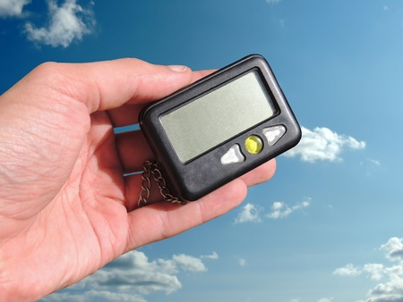 pager in hand against the blue sky