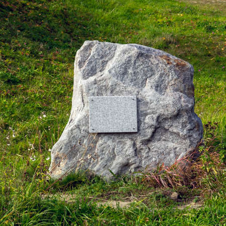 Memorial stone in the grass with a sign 版權商用圖片