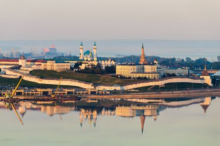 The white-stone Kazan Kremlin at sunset. Wall lit by the sun and reflected in the water